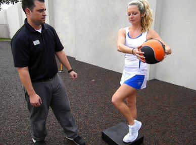 Picture of therapist treating tennis player performing medicine ball exercise