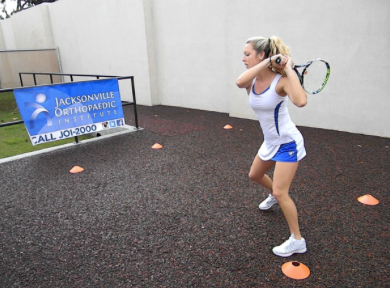 Picture of tennis player performing lateral cone exercise with raquet