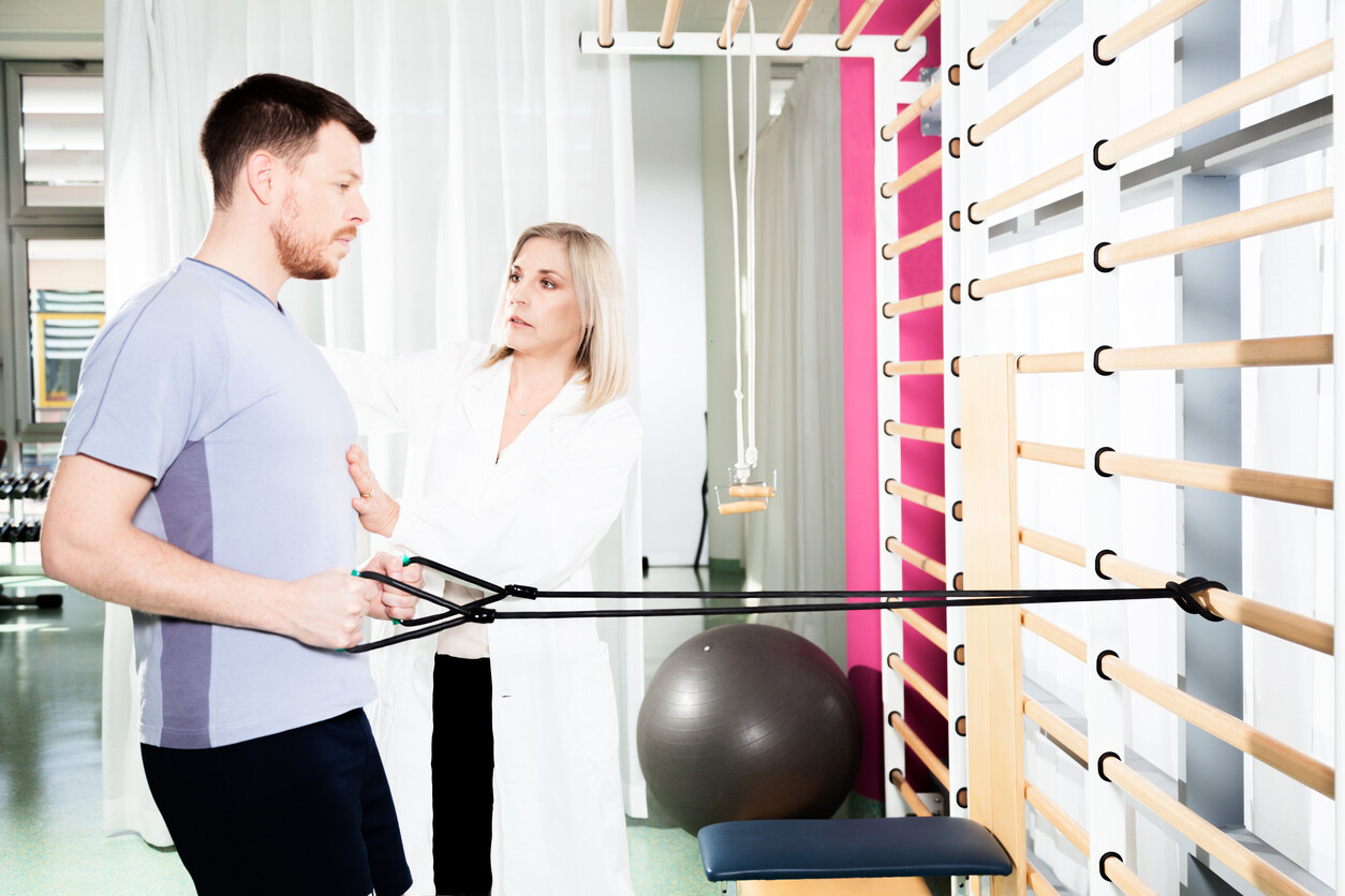 Therapist talking to patient while patient perform band resisted rows