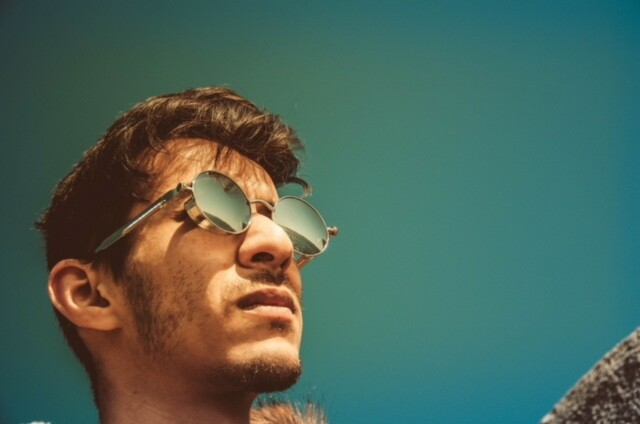 Guy wearing sunglasses outside looking into the sun